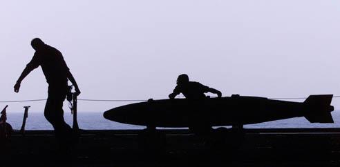 Soldado puxa uma bomba no porta-aviões Carl Vinson, um dos que estão em uso no ataque dos EUA ao Afeganistão. (Foto: Jim Hollander - 30.out.2001/ Reuters)