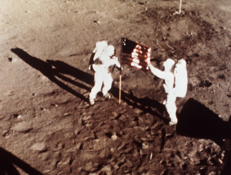 "ORG XMIT: 123001_1.tif Os astronautas Neil Armstrong e Edwin Aldrin fincam bandeira dos EUA na Lua, em julho de 1969. Apollo 11 astronauts Neil Armstrong and Edwin E. ""Buzz"" Aldrin, the first men to land on the moon, plant the U.S. flag on the lunar surface, July 20, 1969. Photo was made by a 16mm movie camera inside the lunar module, shooting at one frame per second. (AP Photo/NASA)"