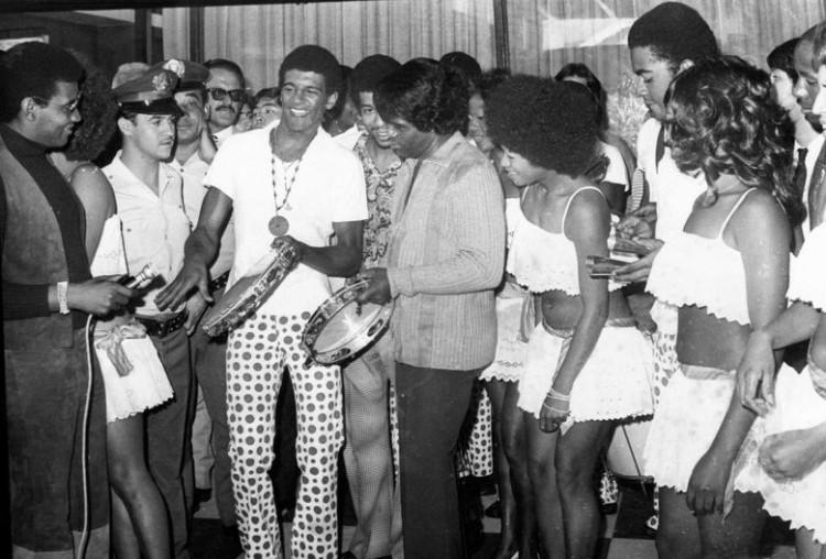 O cantor norte-americano de soul e funk, James Brown, tenta tocar pandeiro ao lado de Wilson Simonal (à esquerda) e  sambistas brasileiras após desembarque no aeroporto de Congonhas, em São Paulo (SP). (São Paulo (SP), 29.03.1973. Foto: Acervo UH/Folhapress)