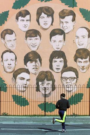 """Jovem passa em frente ao mural das vítimas do """"Domingo Sangrento"""", em Londonderry (Irlanda do Norte) (Foto: Peter Morrison - 27.mar.2000/Associated Press)"""
